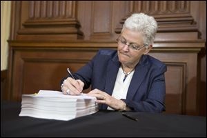 Environmental Protection Agency Administrator Gina McCarthy signs new emission guidelines during an announcement of a plan to cut carbon dioxide emissions from power plants by 30 percent by 2030, today, at EPA headquarters in Washington.