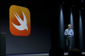 Apple senior vice president of Software Engineering Craig Federighi walks next to a symbol for Swift, a new programming language, while speaking at the Apple Worldwide Developers Conference today in San Francisco.
