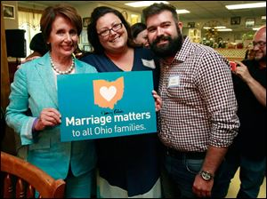 House Minority Leader Nancy Pelosi holds a Marriage Matters sign she signed.. She is with Marriage Matters advocates Sheena Kadi and Nick Komives.