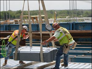 Ironworkers from Local 25 Charlie Bunker, left, and Jason Harris direct a load of stay in place forms onto the work surface.