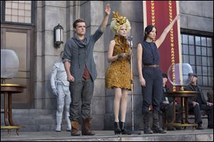 From left,  Josh Hutcherson as Peeta Mellark, Elizabeth Banks as Effie Trinket and Jennifer Lawrence as Katniss Everdeen in a scene from the film,