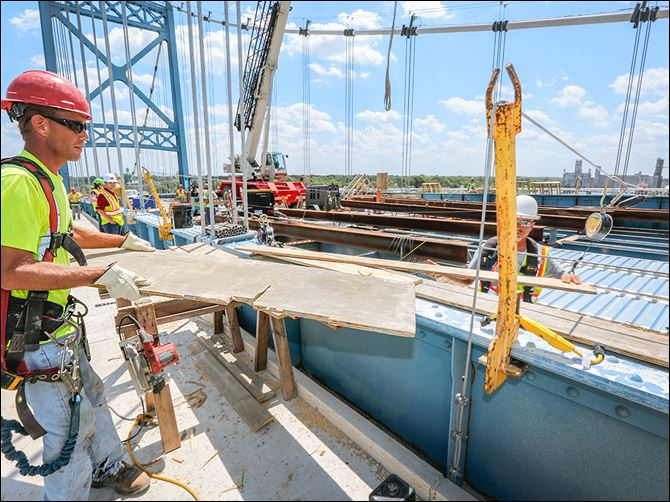 n4bridge Eric Johnston of Norwalk passes a board to Marty Goon of Genoa, partially obscured, at work on the Anthony Wayne Bridge, which connects East Toledo to the rest of the city. Often called the High Level Bridge, it was built in 1931.