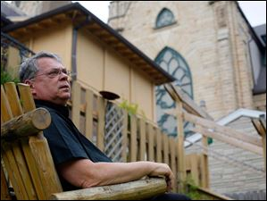 Father Christopher Vasko, a Catholic priest at Historic St. Patrick's, enjoys sitting near the pond the backyard of the Historic St. Patrick's Church.