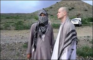 Sgt. Bowe Bergdahl, right, stands with a Taliban fighter in eastern Afghanistan. The Taliban released a video today showing the handover of Bergdahl to U.S. forces in eastern Afghanistan.