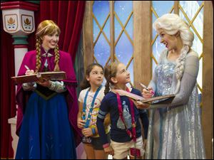 Disney characters Anna, left, and her sister Elsa from the animated film '‍Frozen' meet with two young fans at the Norway Pavilion at Walt Disney World Resort in Lake Buena Vista, Fla.