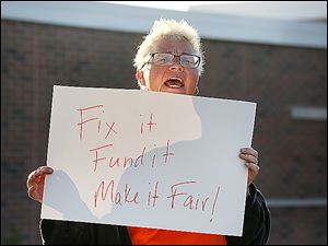Shannon Conway, a TARTA worker, rallies outside TARTA headquarters. The slogan on her sign refers to TARTA's funding system and the employees who are working under an expired contract.