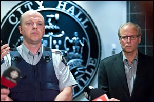 Royal Canadian Mounted Police officer Damien Theriault and Mayor George LeBlanc pause to collect themselves before addressing the media during a late night news conference at City Hall in Moncton,  New Brunswick  Wednesday.