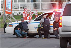 Police officers take cover behind their vehicles in Moncton, New Brunswick, on Wednesday.searching for a suspect.