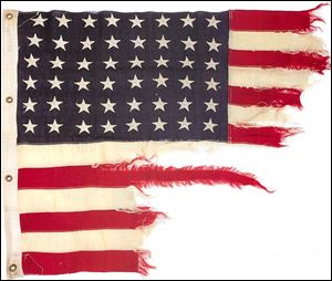 A tattered 48-star American flag that flew aboard the U.S.-built LST 493 on D-Day.