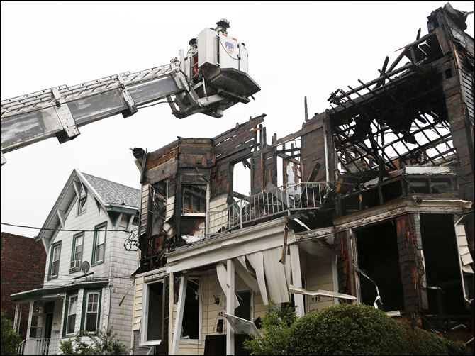 Staten Island Fire A firefighter uses a ladder to examine the damaged roof of 203 and 205 Chestnut Avenue in the Staten Island borough of New York, today, after fire tore through three adjacent townhouses injuring 34 people.