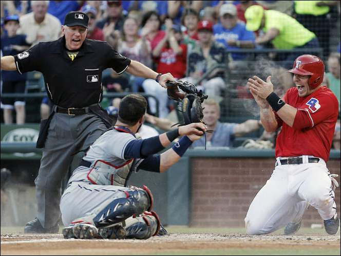 Home plate umpire Lance Barksdale, left, signals safe as Texas Rangers Chris Gimenez, right, celebrates scoring a run after Cleveland Indians catcher Yan Gomes missed the tag.