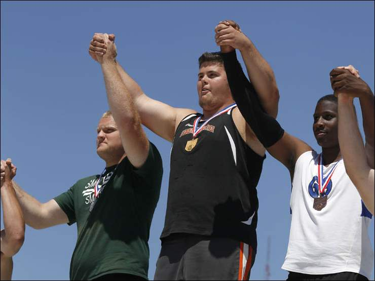Liberty Center's Nick Demaline, center, celebrates his 1st place victory in the Div. III shot put event with other placeholders on the podium.