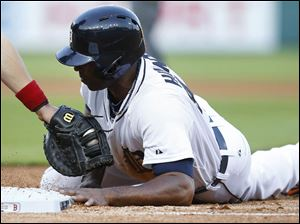 Torii Hunter dives safely back into first base under the tag of Boston Red Sox first baseman Brock Holt.