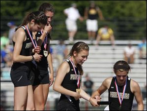 The Perrysburg girls Div. 1 4x800 meter relay champions exits the 1st place podium spot after receiving their medals.
