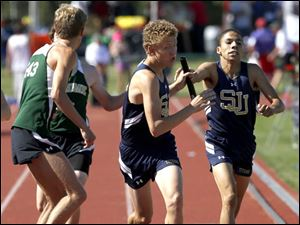 St. Johns' Nicholas Jarrell gets the baton from Tevin Brown in the Div. 1 4x800 meter relay.