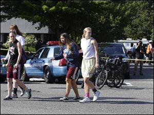Students help each other as they walk away from the scene of a shooting Thursday.