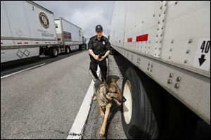 Trooper Ryan Stewart of the Ohio Highway Patrol's criminal patrol team and his narcotics dog Oso search a tractor-trailer on the Ohio Turnpike near milepost 69. The driver and truck were released.
