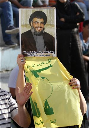 Syrian people from Julan and Palestinians hold a poster of the leader Hassan Nasrallah and the Hezbollah flag during a rally to support Syria in Balata refugees camp in the West Bank city of Nablus.