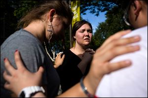 Following the lift of a lockdown in the wake of a school shooting, Seattle Pacific University students pray together.