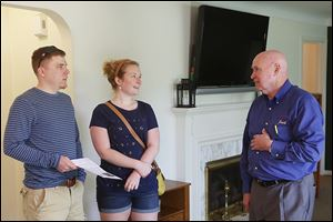 Adam Bachorik, left, and Erica Davis, both of West Toledo, talk with RE/MAX Realtor Jack Schroeder during an open house Mr. Schroeder was showing a West Toledo home listed for $149,000.