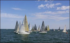 Boats competing in the President's Trophy Course cross the start line at the Toledo Harbor Light for the Mills Trophy Race.