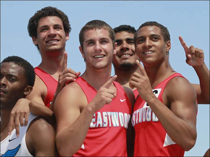 The Eastwood Div. II 4x400 meter relay team celebrates their victory on the podium.
