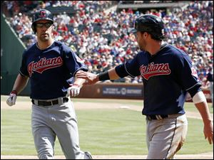 Cleveland Indians' Jason Kipnis  is congratulated by David Murphy after scoring on Murphy's sacrifice-fly.