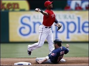 Texas Rangers shortstop Elvis Andrus, left, throws to first after forcing out Cleveland Indians' Jason Kipnis, right, on a ball hit by Lonnie Chisenhall.