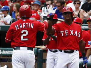Rangers' Leonys Martin (2) is congratulated by Adrian Beltre, right, after scoring on a sacrifice fly by Elvis Andrus.