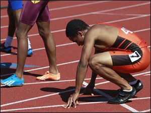 Southview's Malcolm Johnson stretches a pulled muscle after placing 3rd in the Div. 1 100 meter dash.