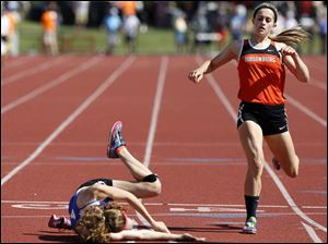 A runner falls as Gibsonburg's Colleen Reynolds places 4th in the Div. III 400 meter dash.