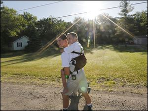 Hunter Gandee, 14, began a 40-mile walk to Ann Arbor on Saturday, carrying his brother Braden, 7, on his back.