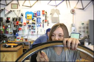 Shop assistant Alanna Cromley replaces a tube while working on restoring an old bike.