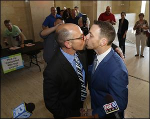 Rich Gillard, left, and Andrew Petroll kiss after their marriage ceremony at the Milwaukee County Courthouse.