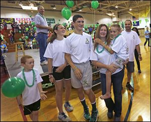 The Gandee family, from left, Kellen, Kerragan, Hunter, mom Danielle carrying Braden, and dad Sam, welcome more than 300 supporters at Bedford Junior High School on Saturday as Hunter, 14, begins his journey to carry his 7-year-old brother, Braden, on his back to Ann Arbor.