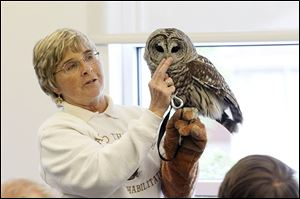 Mona Rutger, shown working with a barred owl, runs '‍Back to the Wild,' a nature hospital for rare and exotic creatures that have been injured.