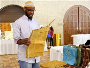 Ashir Kirk of Toledo opens up a prayer rug that was encased in a special bag that he has for sale.