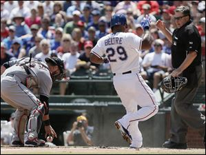 Adrian Beltre is ruled out, after Indians catcher Yan Gomes, left, held onto the ball long enough for the call.