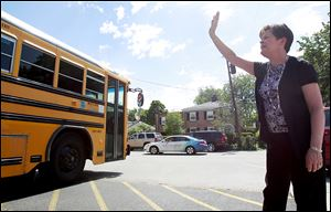 Barbara Jenks, retiring principal at St. Rose School, waves to students as they leave school for summer vacation. Mrs. Jenks has seen many students go from kindergarten to high school in 21 years.