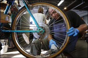 Roy Lee Snow, of North Toledo cleans between the spokes of a bicycle he is helping to restore during a recent open bike night.