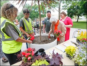 Trudy Price, right, plants flowers in a big pot on the  Bowling Green University Hall lawn in celebration of her 100th birthday with help from Barb Brown, left, and Jake Stock,center left, with Campus Operations, Tracy Ricard, LPN,  center right, and Christine Burger, right.