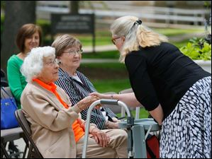 Sterling House of Bowling Green resident Trudy Price, left, is greeted by Rebecca Ferguson, right, Chief Human Resources Officer at Bowling Green State University,  before she mows the Bowling Green University Hall lawn in celebration of her 100th birthday. Price's friend Shirley Smith, center, sits nearby.