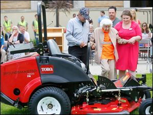 Trudy Price is escorted by Scott Euler, left, and Christine Burger, right, to the Toro Lawn Mower where she will sit before using a push mower to mow the Bowling Green University Hall lawn.