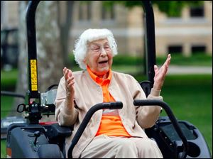 Trudy Price sits in on the motorized lawn mower on the Bowling Green University Hall lawn in celebration of her 100th birthday.