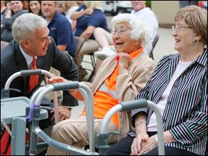 Sterling House of Bowling Green resident Trudy Price, center, is greeted by Sen. Randy Gardner, left, before she mows the Bowling Green University Hall lawn.
