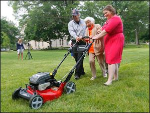 Trudy Price mows the he Bowling Green University Hall lawn in celebration of her 100th birthday with help from  Scott Euler, left, and Christine Burger, right.