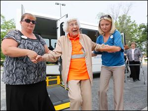 Sterling House of Bowling Green resident Trudy Price, center, is escorted by Trish Hosley, LPN, left, and Jessi Chapman, program, coordinator, right, to the Bowling Green University Hall lawn.