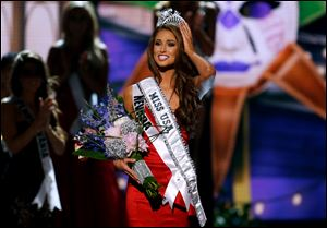 Miss Nevada USA Nia Sanchez adjusts her crown after  being crowned the new Miss USA during the Miss USA 2014 pageant in Baton Rouge, La., Sunday.
