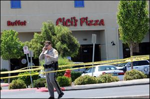 A Las Vegas police officer walks near the scene of a shooting in Las Vegas, Sunday. The spree began around 11:30 a.m. Sunday when a man and woman walked into CiCi's Pizza and shot two officers who were eating lunch, Las Vegas police spokesman Larry Hadfield said.