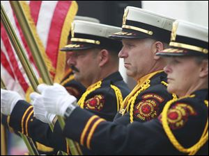 Toledo honor guard member Craig Ellis, center, presents the colors with other honor guard members at the start of the Toledo Fire Department's annual memorial service.